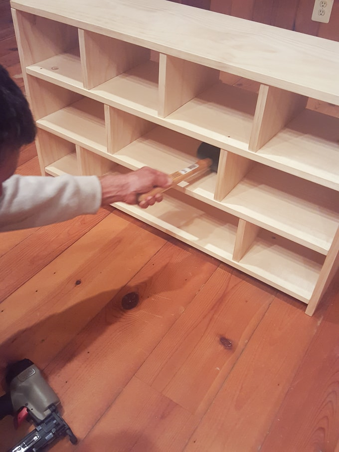 hammering a DIY shoe cubby dividers into place