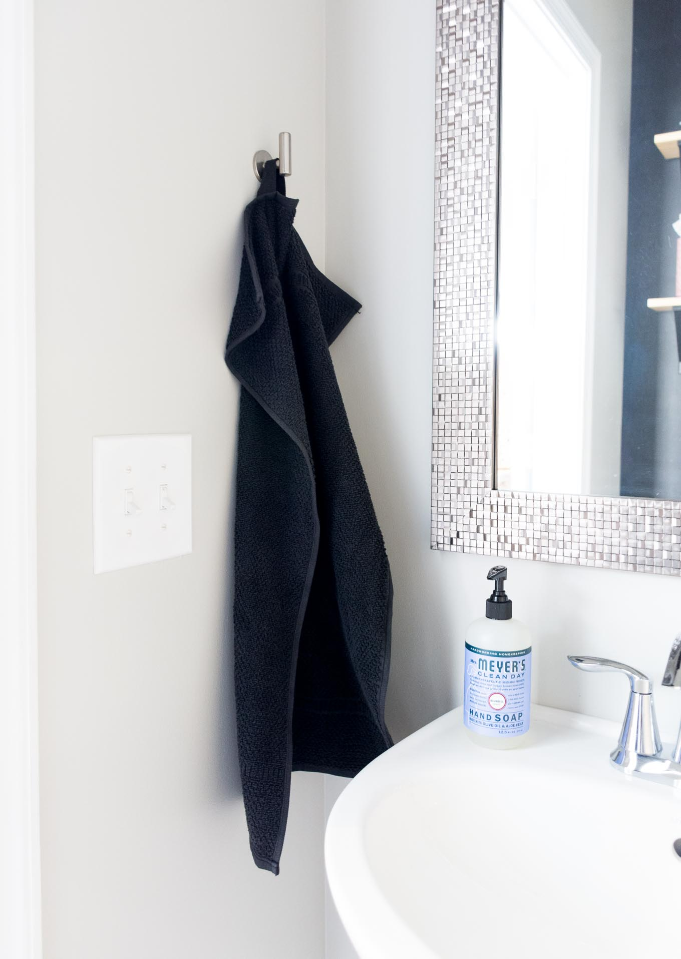 Modern powder room makeover on a budget with black walls and a glam mirror // black powder room, Sherwin-Williams Tricorn Black, black bathroom, small bathroom ideas, bathroom open shelving