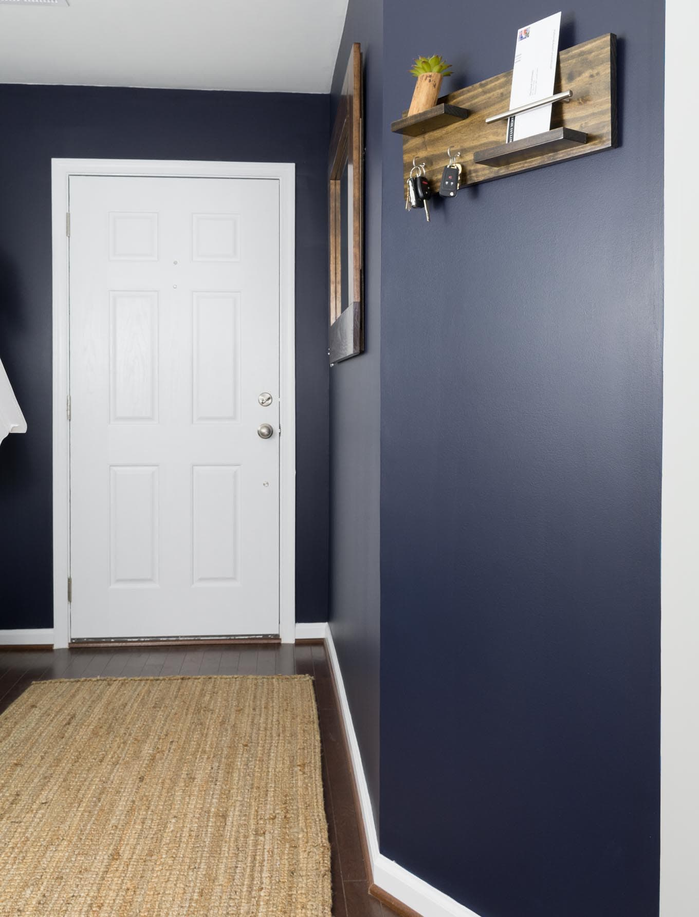 Check out this small and modern navy entryway makeover using Sherwin-Williams paint in Anchors Aweigh and Repose Gray.