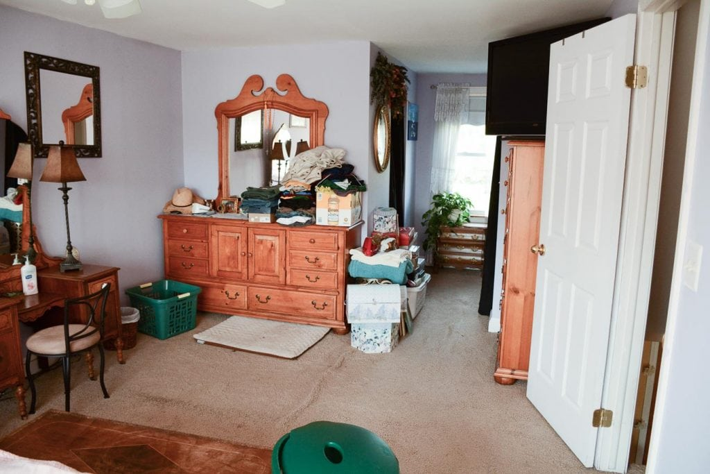 dated master bedroom with lilac walls