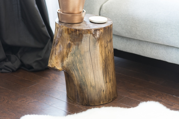 Learn how to make a tree stump side table by staining and finishing a stump! It's easy and way cheaper than buying one in a store...just takes a little patience! | diy tree stump side table