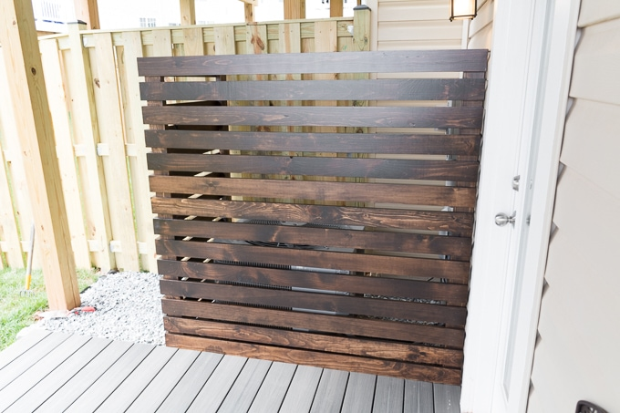 "Hi guys, it's week 3 of the One Room Challenge, and we're finishing up the AC/utilities corner part of the yard. Wahoo! Last week, I shared progress on the platform deck and some light rock landscaping. This week, I'm sharing the DIY AC unit screen I made. I'm going to share how I did it, but I'm not going to share a complete tutorial. It's unlikely that anyone (except my next door neighbor) has exactly the same layout and needs as we do. Here's what we used to make a DIY AC unit screen: (Affiliate links below. Thank you for your support!) 2x4s for the standing pieces 1x4s for the slats Random orbit sander Fine-frit sandpaper to polish by hand Saw, finish nailer Liquid Nails Heavy Duty Construction Adhesive Varathane wood stain in Kona Minwax Helmsman Spar Urethane in Satin Kreg Jig and 2.5"" pocket hole screws And here's how we did it. (Remember to wear a mask and eye protection while sanding and working with wood, and wear an appropriate mask while working with stains and finishes. Follow the directions and warnings from your particular brand. Do not use any tools without proper training, precautions, and supervision. Read my full disclaimer here.) Step 1: First we measured how big we wanted the screen to be. We decided to shape it like an L and have it come up high enough to cover other utilities, not just the AC unit. (If you make a project like this, make sure it does not interfere with anything that requires air circulation or regular reading.) After deciding on measurements, and knowing we wanted each screen slat to be 1 inch apart, we calculated how much 1x4 we'd need. Once we had the final height (14 pieces of 1x4, each an inch apart), we cut the four pieces of 2x4 to height. (Yes, that's a diaper and a package of wipes in my purse. Times have changed.) Step 2: Next I gave each piece a quick sand using my random orbit sander. This was mostly to polish each piece up and break down any rough or splintery edges. After each piece was cleaned up, I wiped the whole lot down and stained each using the Varathane wood stain in Kona. I also drilled pocket holes in one of my 2x4s to create the main corner support (but didn't attach them yet). This, coupled with the next step, was by far the most time consuming. (But was faster using a small roller instead of a paint brush!) I was VERY GLAD at this point that I hadn't used 1x2 like I'd originally wanted. That would have been painful. Step 3: Once I had stained everything and it had dried according to my instructions, I gave each piece a few coats of the Minwax Helmsman Spar Urethane in Satin. Oof, talk about a slow process. (See my post on how to stain and finish wood here.) And one that took over my garage for several days. Luckily the urethane dries in about 4 hours, so that helped me get two coats in on one day. Everything is dry...time to assemble. Yay! Step 4: We began working on the longer side of our L-shaped screen first. Board by board, we spaced and nailed using a finish nailer. (By we, I mean my dad, who came over with his finish nailer to help me complete this project. Ramona was up, so I held her while she watched from inside. She loves grandpappy.) We did a 3/4"" overhang on the left side. You'll see why. Step 5: Once the longer side was done, we did the shorter side. For those, we did a 1.5"" overhang on the right side. Step 6: We stood the screen up to make sure everything looked right. Now here's where the pocket holes came in handy. We attached each side to one another by driving 2.5"" pocket hole screws through the pocket holes. Since we also built an overhang in on each side, the sides fit together perfectly. And here it is in place! It fits perfectly over the L shape of pavers we laid and is perfectly level. I am super pleased with how this one turned out. It may have been time consuming, but it was worth it! And it matches the outdoor table and benches I'll be sharing soon. PIC You can also see I decided to dress it up a bit with some Pot Clips and pots we had in the garage. I love these things. Like this? PIN IT!"