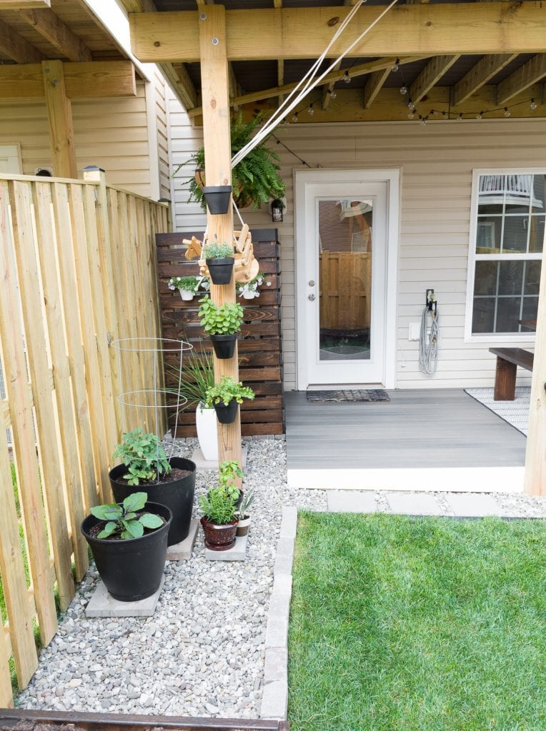 Modern design ideas for a small backyard // DIY rock landscaping around a gray Trex platform deck // Hanging herbs