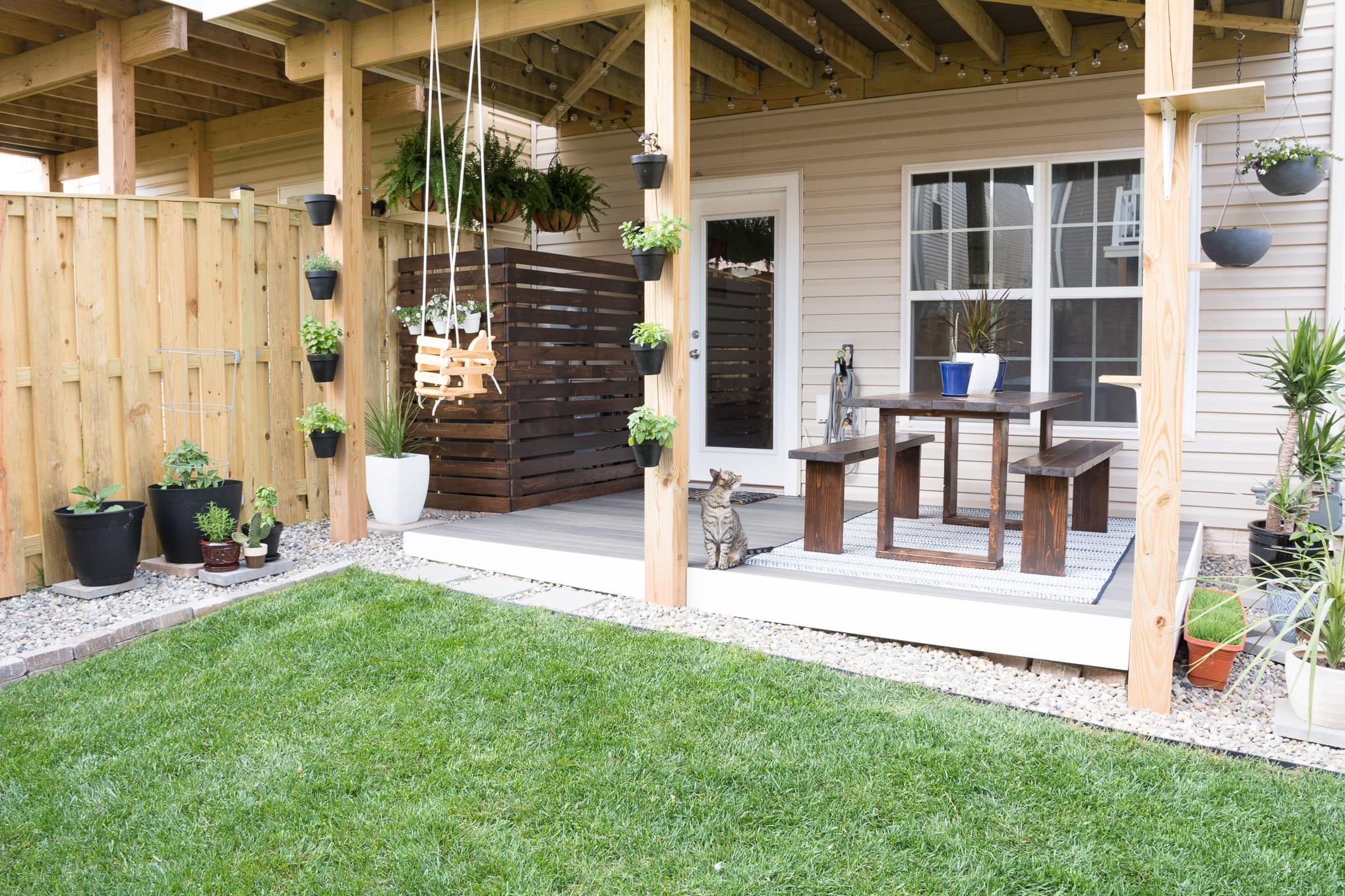 Modern design ideas for a small backyard // DIY rock landscaping around a gray Trex platform deck // Hanging herbs // DIY outdoor cat perches // DIY HVAC unit screen // small garden ideas // hanging ferns on a patio