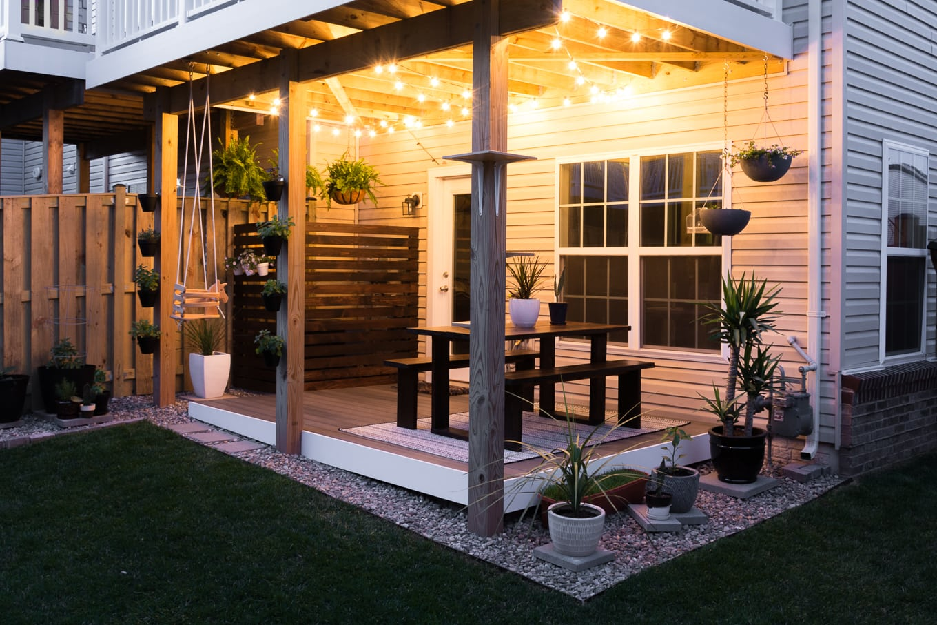 Modern design ideas for a small backyard // DIY rock landscaping around a gray Trex platform deck // Hanging herbs // DIY outdoor cat perches // DIY HVAC unit screen // small garden ideas // hanging ferns on a patio // hanging globe string lights