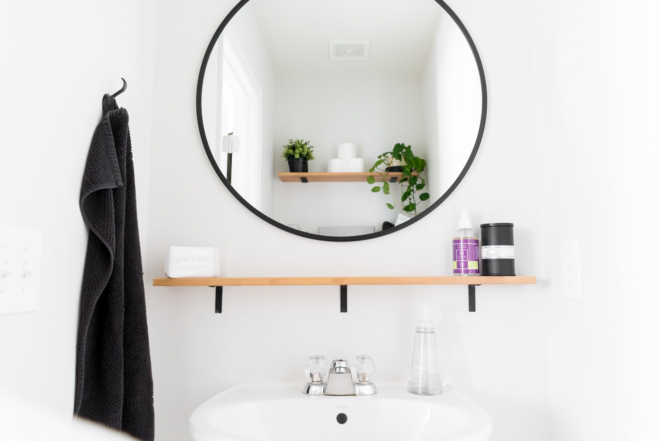 Tiny monochrome powder room with plants, open shelving for storage, a pedestal sink, and a round mirror #diy#monochrome #modern #scandi #scandistyle
