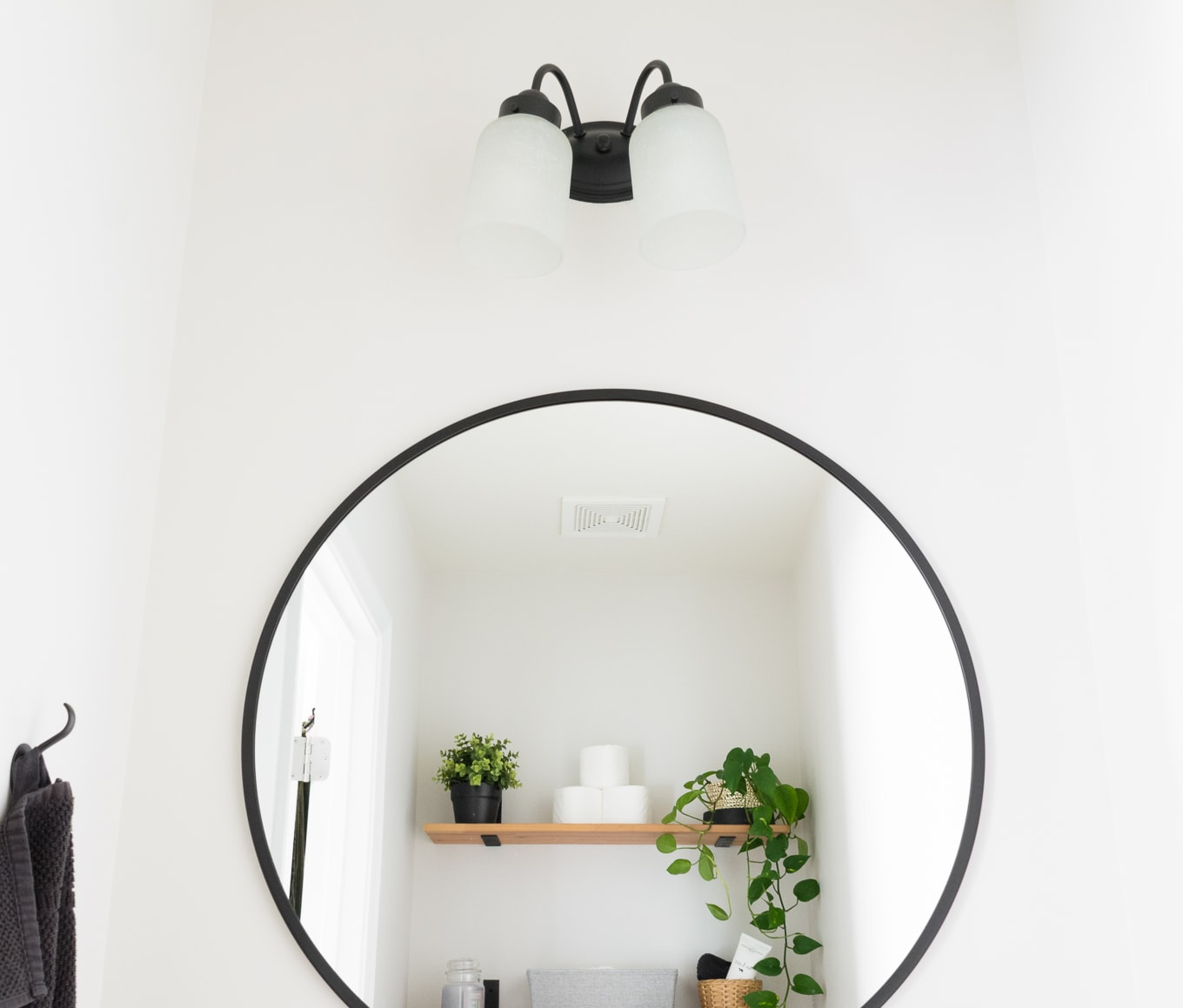 black circular mirror in a half bath