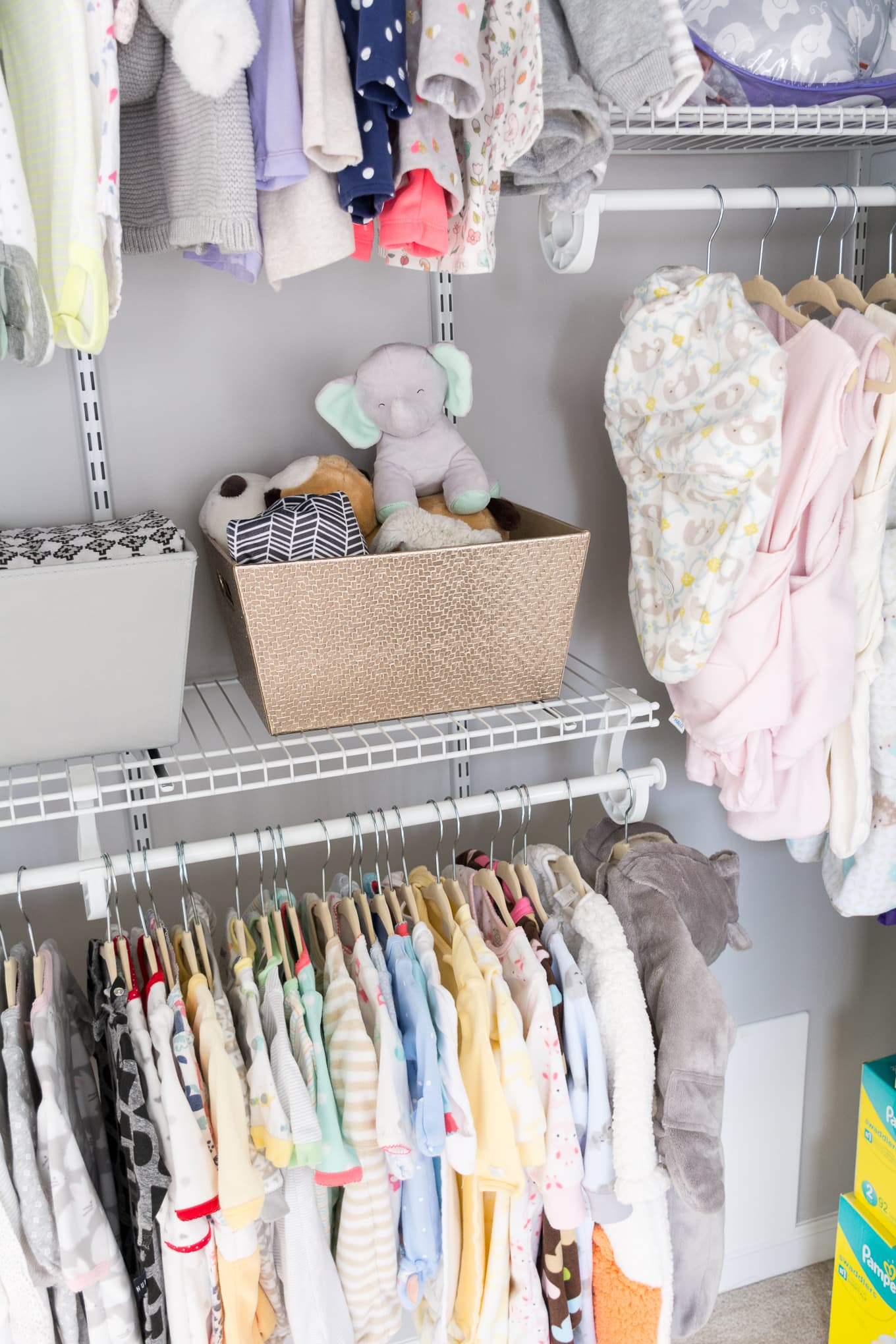 Baby clothes hanging in an organized closet