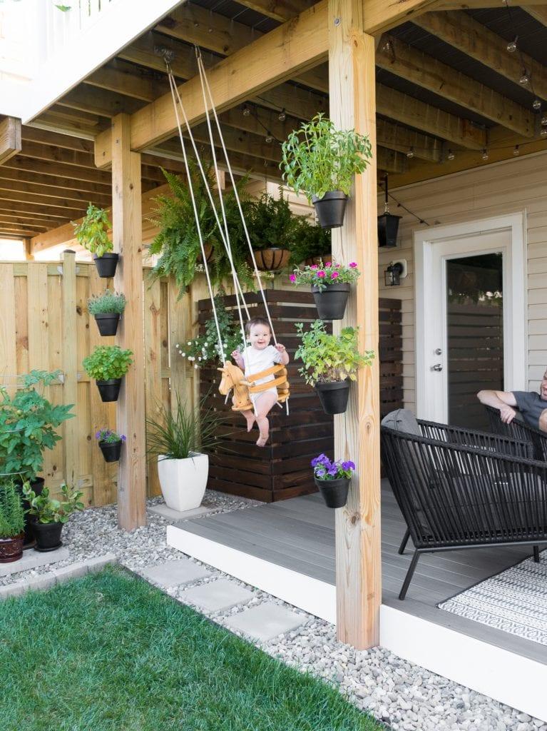 happy baby swinging on a wooden horse swing in a cute backyard