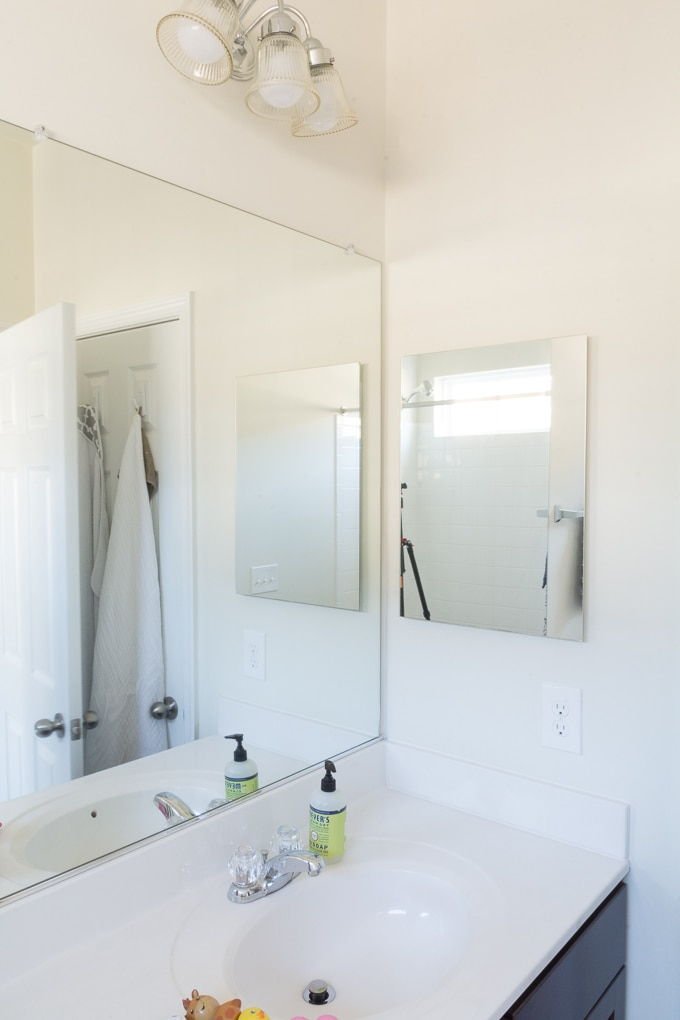 bare mirror with clips in a bathroom