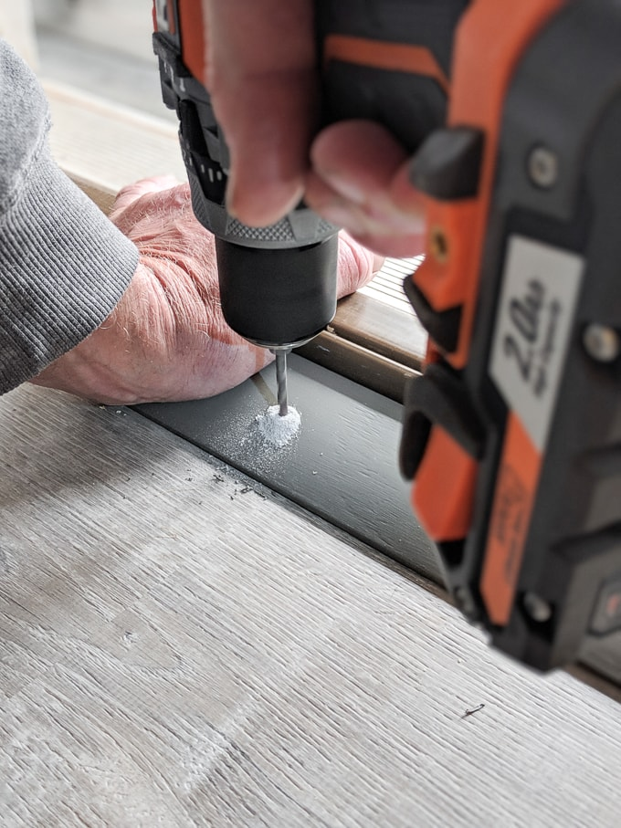 Drilling through the holes in the door threshold into the concrete subfloor