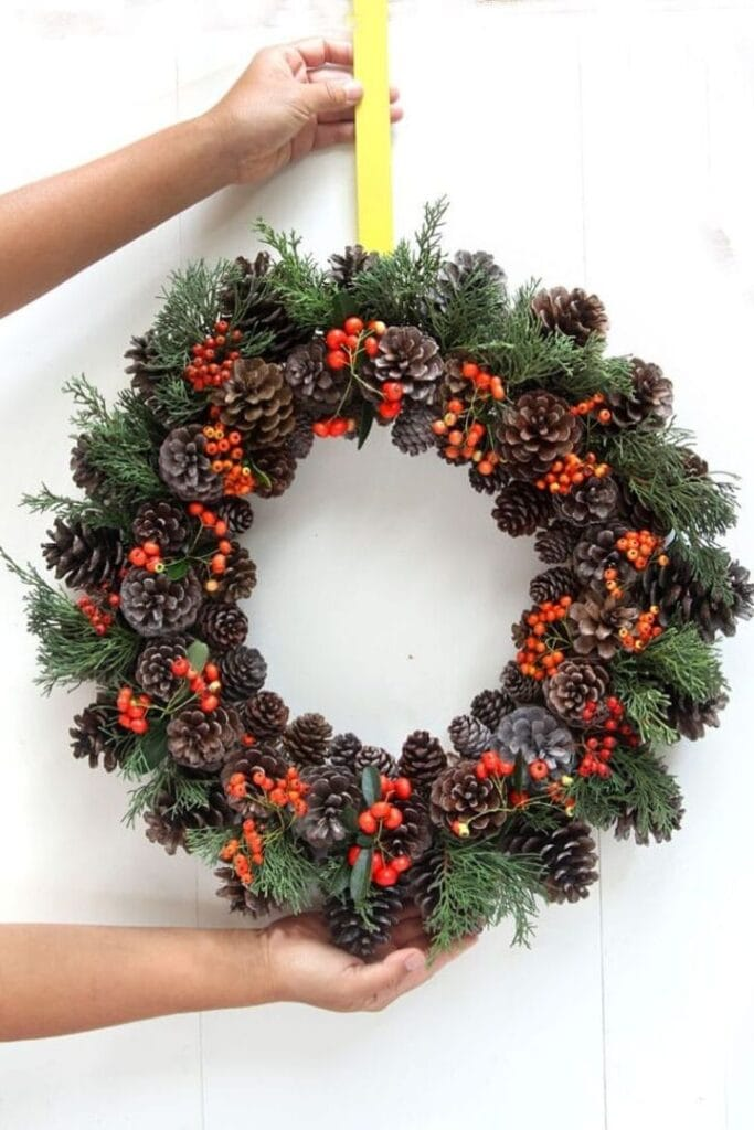 Pine cone wreath with greenery and red berries