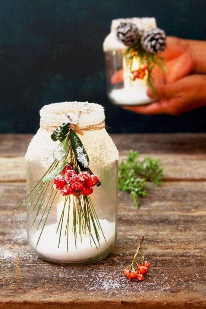 Mason jar with evergreen sprig with berries, frosted glass with candle inside