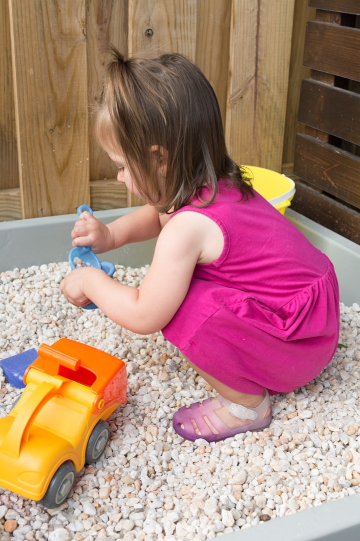 little girl playing in a DIY rock box
