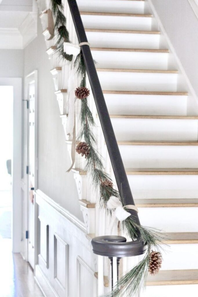 Stair banister decorated with a pine bough garland and pine cones
