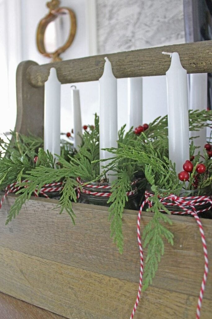 Fresh pine garland decorating jars with candles inside an old wooden toolbox