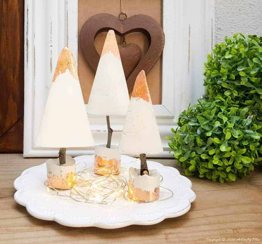 3 concrete Christmas trees with gold dipped tops sitting on a tray