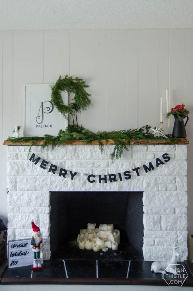 Modern Christmas decor black Merry Christmas Banner draped on a white fireplace