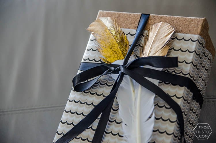 Christmas present wrapped with with a black bow and gold and glitter dipped feathers