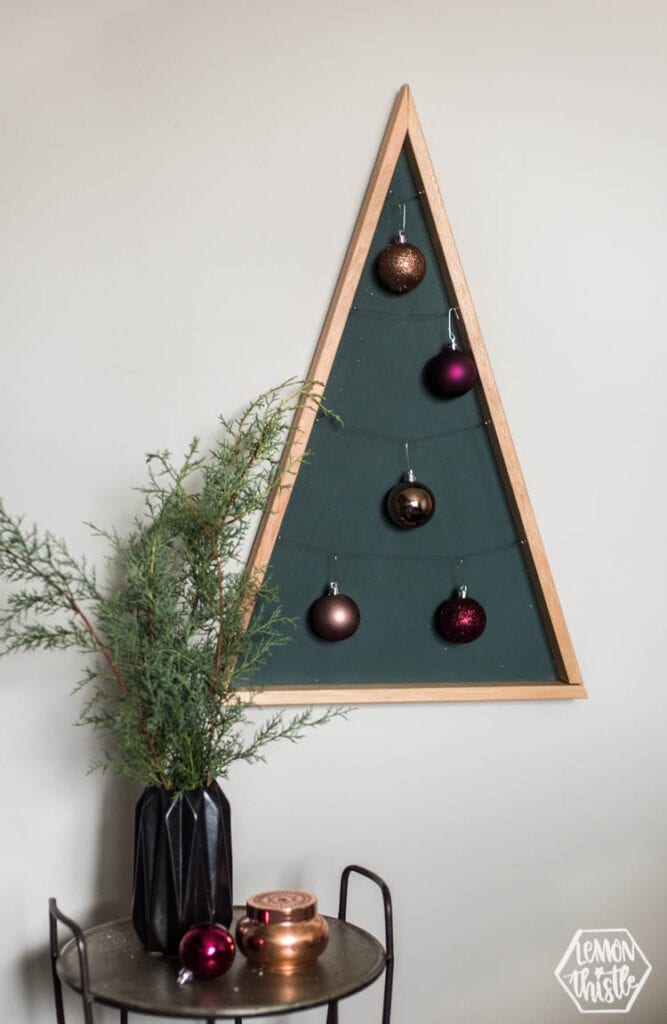 Modern DIY ornament holder made of wood in the shape of a triangle with ornaments hanging on it.
