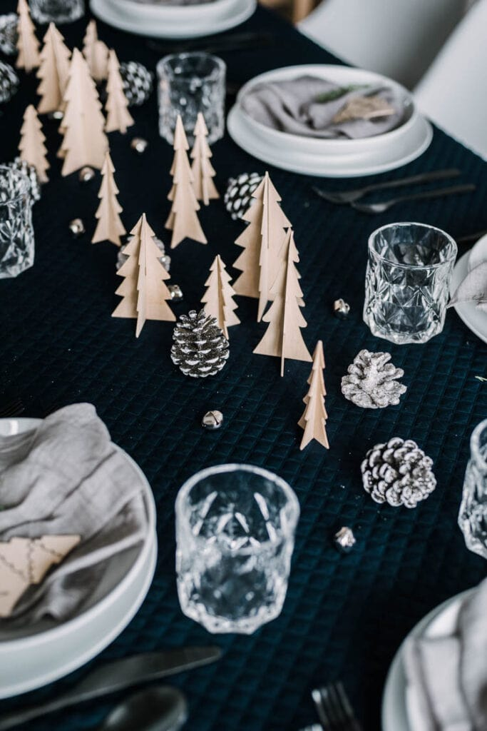 Modern Christmas tree table scape with pine cones, dishes, and wooden Christmas Trees on a black tablecloth