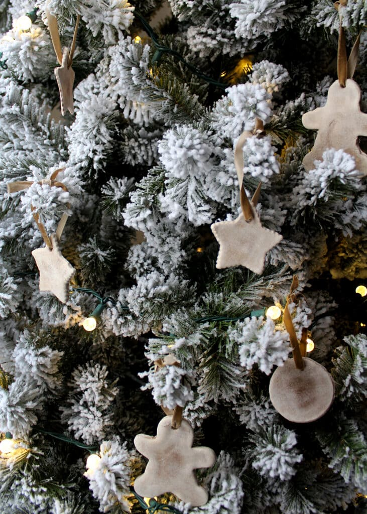 Salt dough ornaments hanging on a frosted Christmas tree
