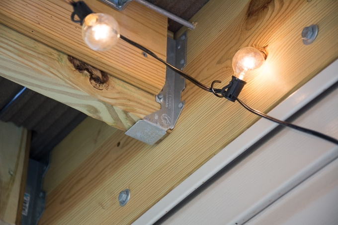 Modern design ideas for a small backyard // how to hang globe string lights under a deck on a patio // #patiodesign #smallbackyard #modernbackyarddesign