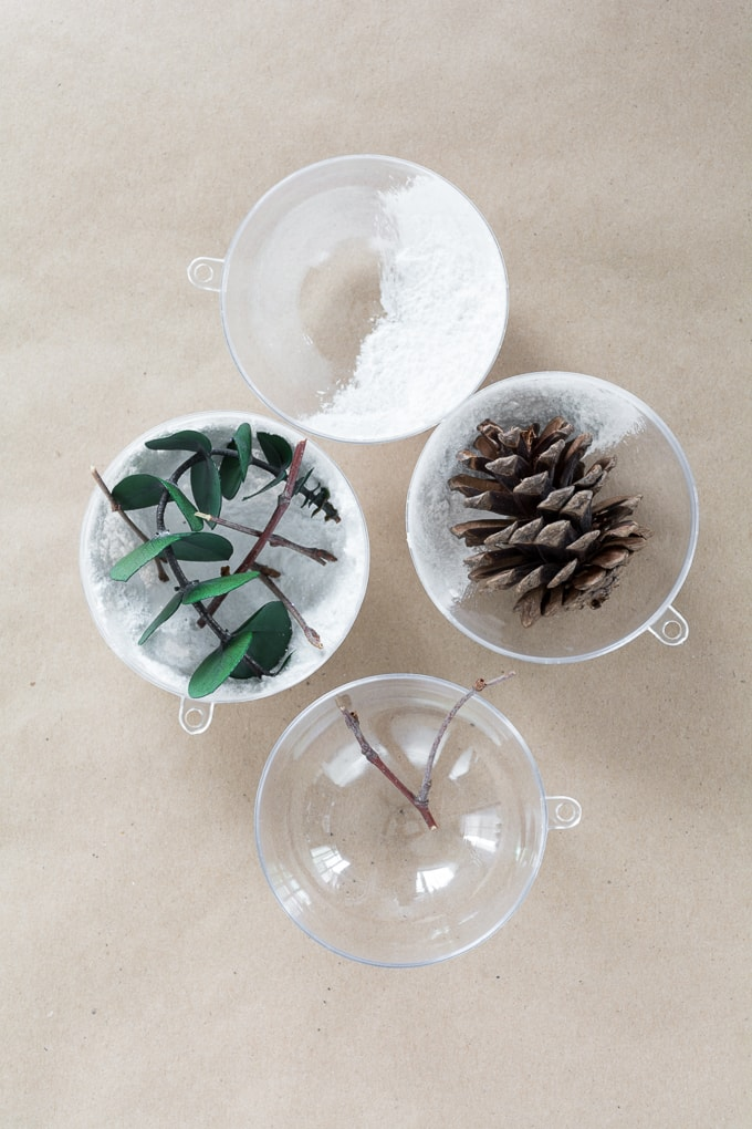 Simple greenery-themed Christmas ornaments using eucalyptus, twigs, and faux snow #christmasornament #christmas #diy #diyornament