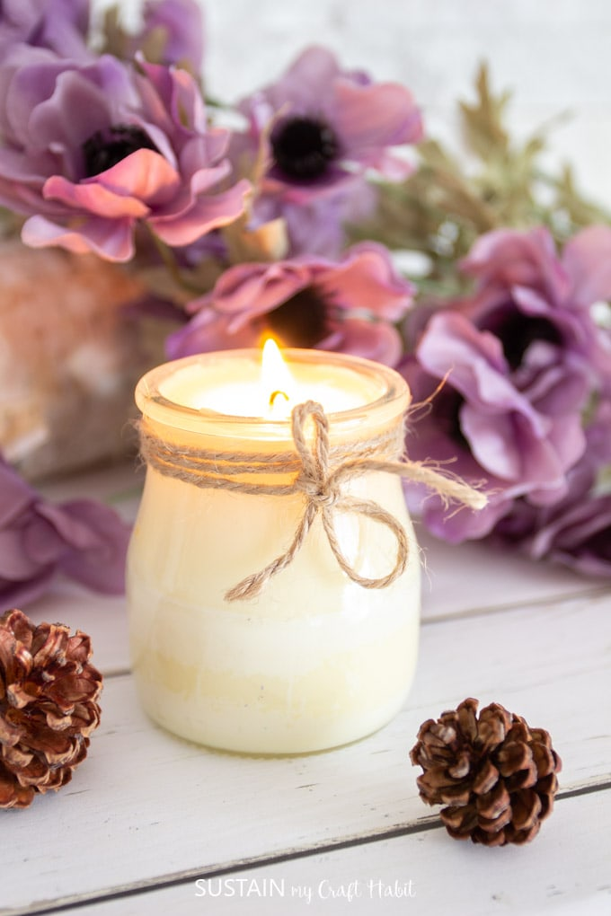orange and cinnamon essential oil candle in a jar with twine wrapped around it