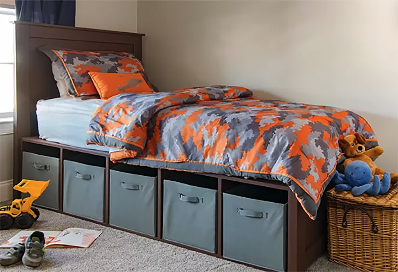 DIY platform bed with orange and gray camouflage sheets