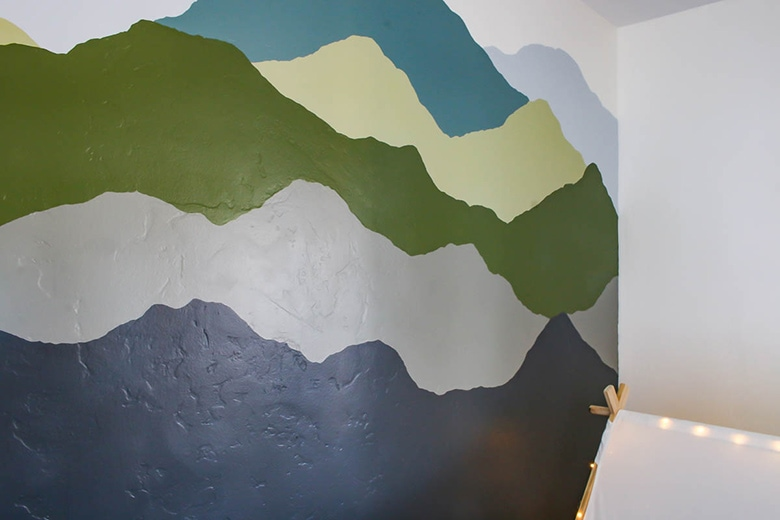 mountain mural painted in blues, greens and grays