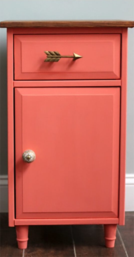 pink painted cabinet with arrow drawer pull