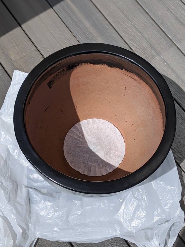 coffee filter in the bottom of a large plant pot