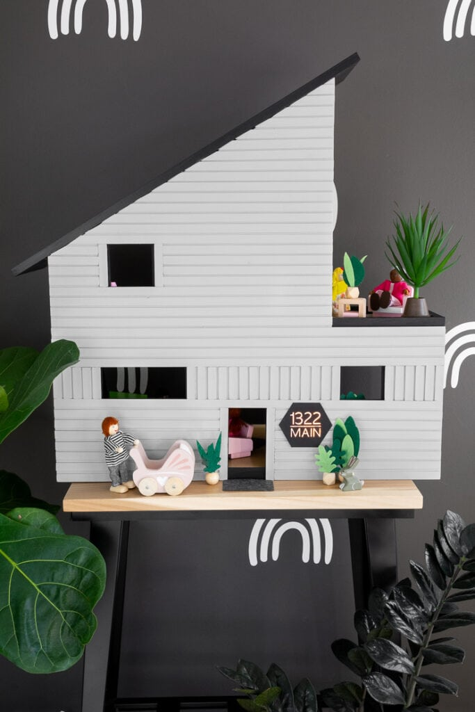 front of a beautiful modern dollhouse