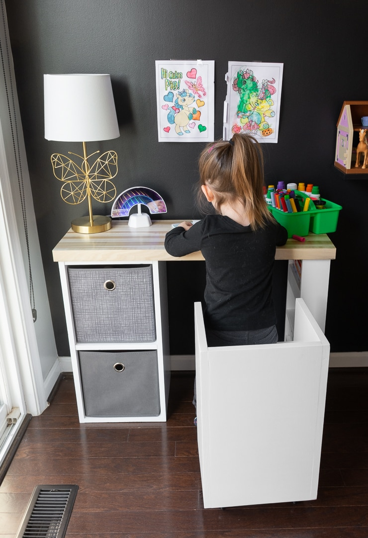 little girl on a DIY kids chair with storage sitting at a desk