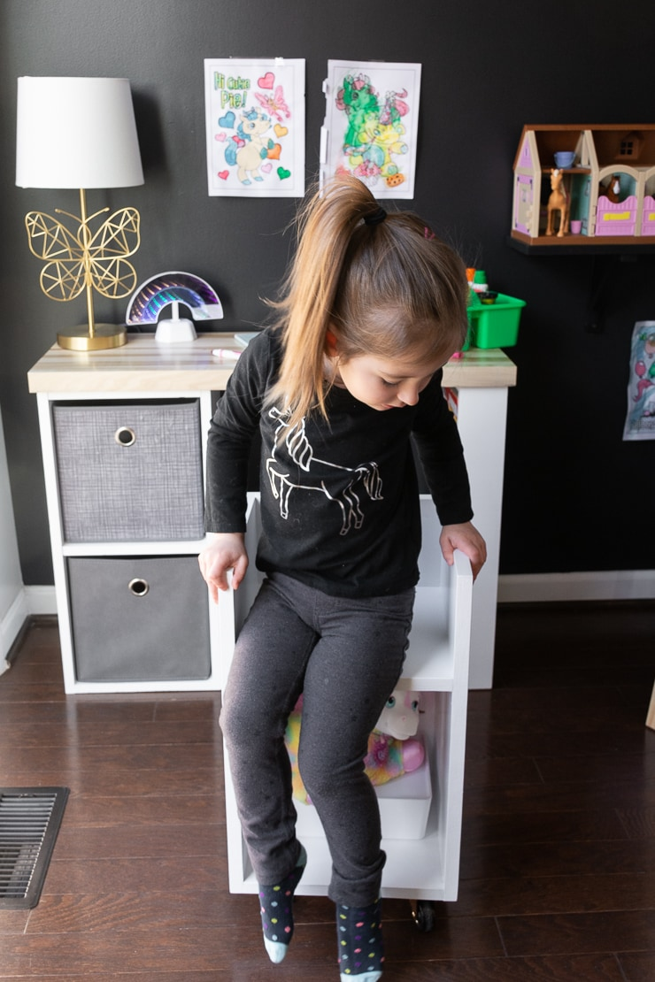 little girl on a DIY kids chair with storage