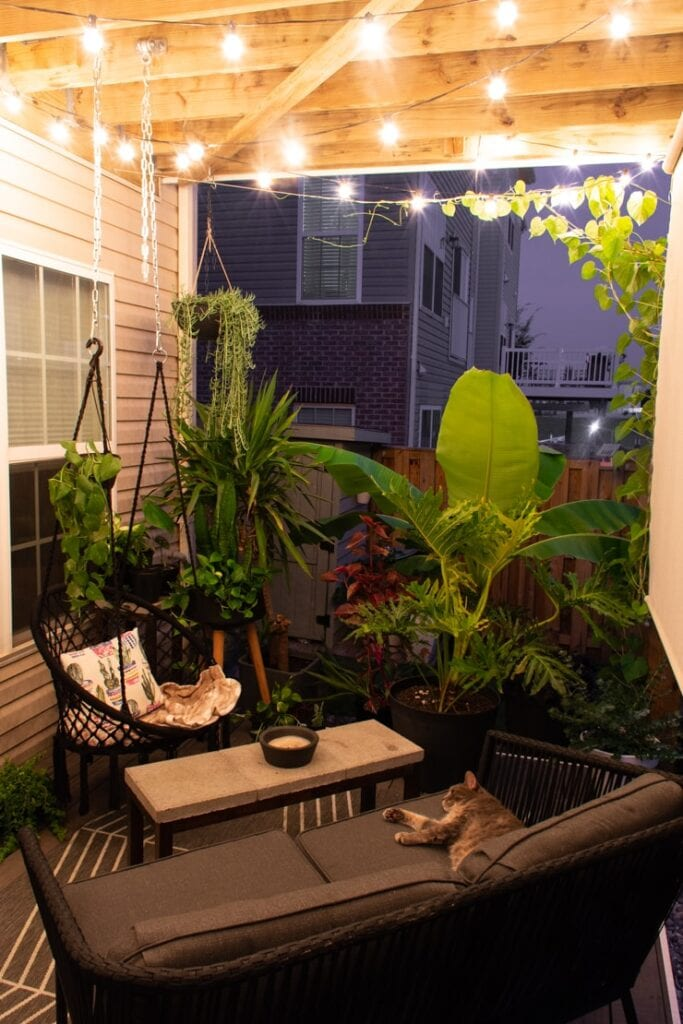 beautiful small patio with hanging globe string lights under a deck and large plants