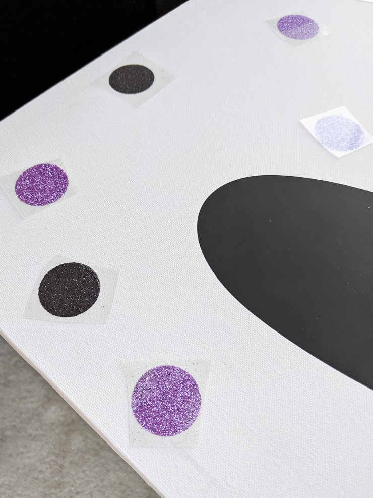 adding glitter circle iron-on pieces onto a canvas to make thrifted kids room decor