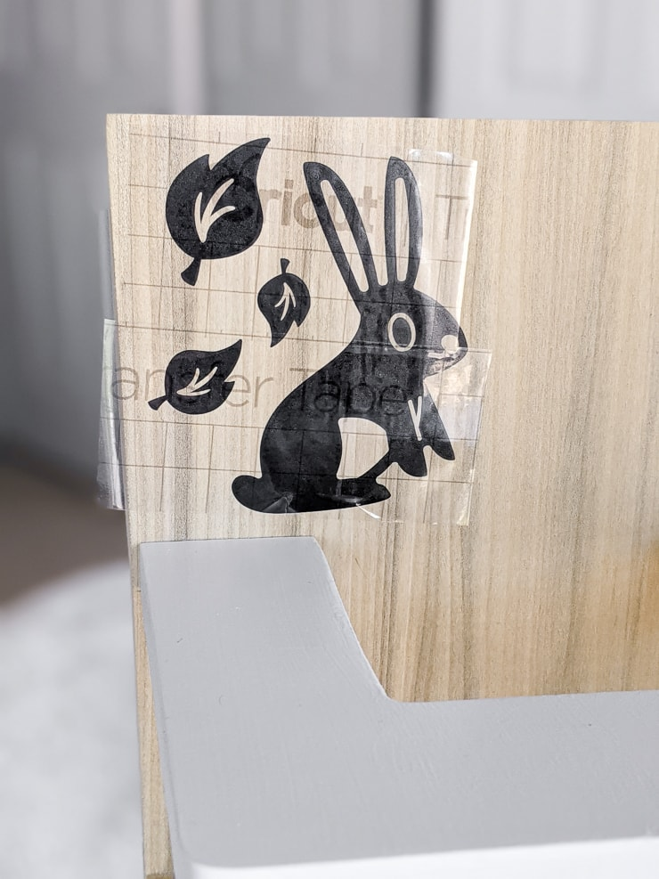 applying a cute decal to the DIY wooden doll high chair