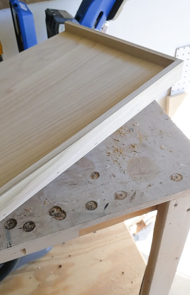 attaching a wooden border around the DIY cat window perch