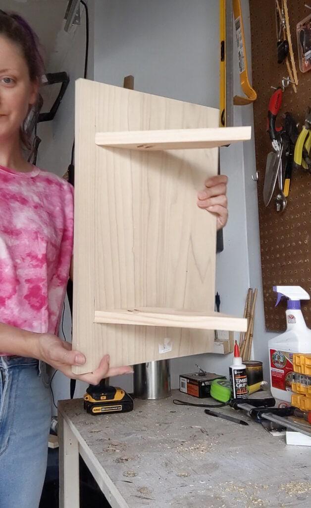 woman holding a DIY cat window perch