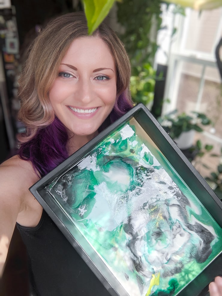 Woman smiling and holding a DIY resin tray
