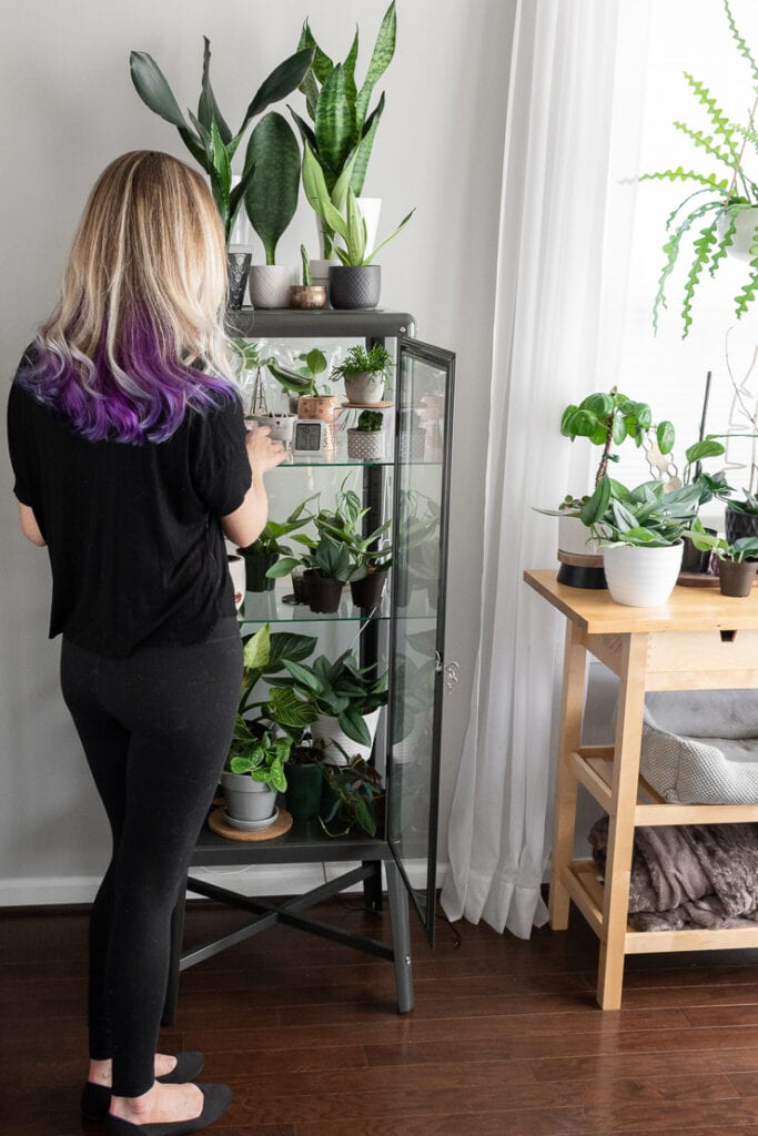 woman tending to plants in an ikea greenhouse cabinet