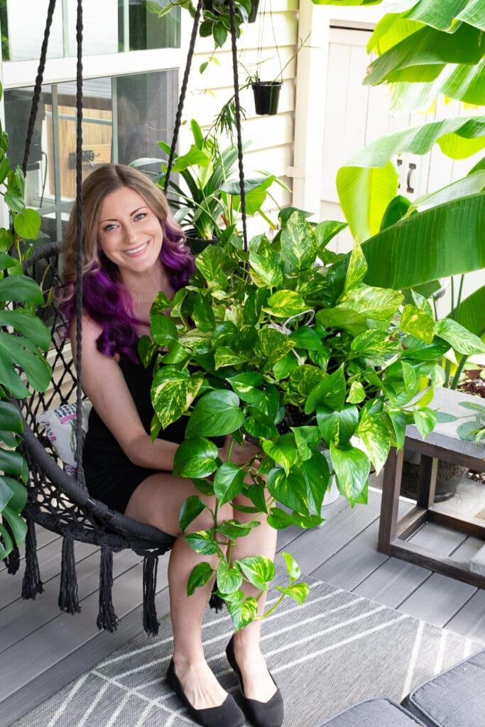 woman holding a large pothos plant